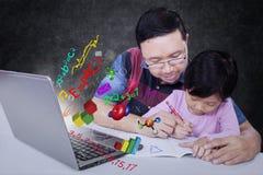 L'uomo aiuta sua figlia a studiare Fotografie Stock