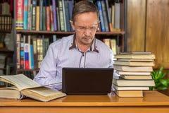 L'uomo all'età che studia nella biblioteca Immagine Stock
