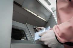 L'uomo alla macchina di BANCOMAT con mette in serbo di credito e delle carte di debito Fotografia Stock