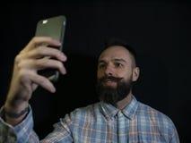 L'uomo alla moda con una barba ed i baffi fa il selfie sul telefono su un fondo nero immagini stock