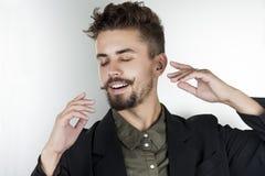 L'uomo alla moda in una camicia in una bella posa sorride vago Immagine Stock