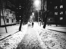 L'uomo alla notte nell'inverno è sul modo Immagine Stock
