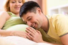 L'uomo allegro abbraccia la pancia della sua moglie incinta immagini stock