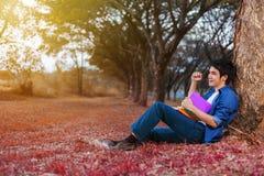 L'uomo allegro che tiene un libro con il braccio si è alzato in parco Immagini Stock Libere da Diritti
