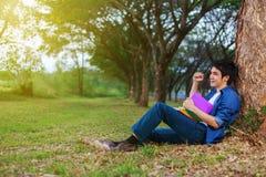 L'uomo allegro che tiene un libro con il braccio si è alzato in parco Immagine Stock