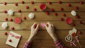 L'uomo allegro con cuore fatto a mano di carta si siede dalla tavola, vista superiore stock footage
