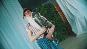 L'uomo allegro in costume nano tiene la tuba rotta della latta nell'ambito del dancing della mano intorno video d archivio