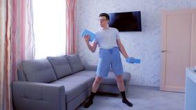 L'uomo allegro del nerd sta facendo gli esercizi per i bicipiti della mano con i blocchetti di yoga invece delle teste di legno c archivi video