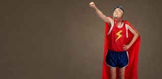 L'uomo allegro divertente divertente in un costume del supereroe negli sport copre immagine stock libera da diritti