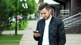 L'uomo allegro moderno utilizza il telefono sulla via archivi video