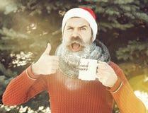 L'uomo allegro nel cappello del Babbo Natale, in pantaloni a vita bassa barbuti con la barba ed in baffi coperti di gelo bianco,  immagine stock