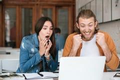 L'uomo allegro sì gesture felicemente mentre ragazza che si siede vicino e che considera amazedly il computer portatile Giovani c immagine stock libera da diritti
