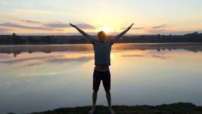L'uomo allegro tiene le mani da parte ed esamina il tramonto nel slo-Mo stock footage