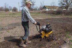 L'uomo allenta il coltivatore del suolo Fotografia Stock Libera da Diritti