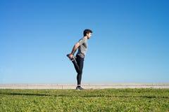 L'uomo allunga la gamba prima di correre Fotografia Stock
