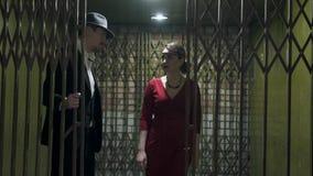 L'uomo alto nel vestito e nel cappello apre la porta ed i passaggi dentro la stanza scura una bella ragazza sicura in un elegante video d archivio