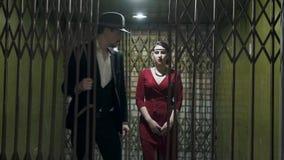 L'uomo alto nel vestito e nel cappello apre la porta ed i passaggi dentro la stanza scura una bella ragazza sicura in un elegante archivi video