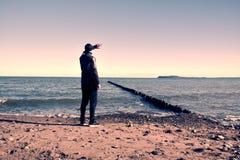 L'uomo alto in vestito nero che si esercita e fa l'allungamento sulla spiaggia pietrosa al frangiflutti Fotografie Stock