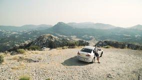 L'uomo ammira la natura i giri argentei dell'automobile su una strada della montagna contro un contesto di una montagna abbellisc stock footage