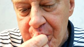 L'uomo anziano affamato veloce ed avido mangia le ali di pollo fritto e felice di rosicchiare le ossa video d archivio