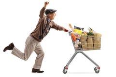 L'uomo anziano allegro che spinge un carrello ha riempito di drogherie Fotografie Stock Libere da Diritti