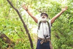 L'uomo anziano allegro ritiene la libertà mentre viaggia nella foresta Fotografia Stock