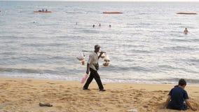 L'uomo anziano asiatico del venditore porta le vendite tropicali dell'alimento sulla spiaggia Pattaya, Tailandia video d archivio