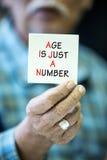 L'uomo anziano asiatico mostra il suo biglietto da visita in bianco fotografie stock
