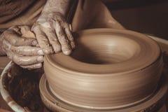 L'uomo anziano che fa il vaso facendo uso delle terraglie spinge dentro lo studio fotografia stock