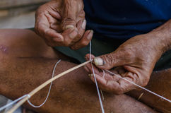 L'uomo anziano che lega una corda per fa un aquilone Fotografie Stock