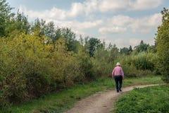L'uomo anziano con il cappello di paglia cammina sopra un percorso stretto immagine stock libera da diritti