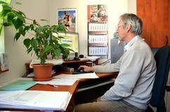L'uomo anziano con il sorriso, un ragioniere, si siede in ufficio e negli impianti con il computer Sulla tavola sono molti docume Immagine Stock Libera da Diritti