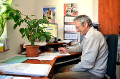 L'uomo anziano con il sorriso, un ragioniere, si siede in ufficio e negli impianti con la penna in sua mano Sulla tavola sono mol Immagini Stock Libere da Diritti