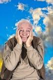 L'uomo anziano copre il suo fronte di sue mani Fotografia Stock Libera da Diritti