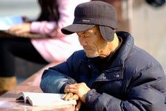 L'uomo anziano di Ya'an Cina-Un sta esaminando un libro sotto il sole Fotografia Stock