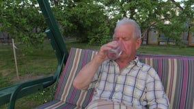 L'uomo anziano e dai capelli grigi che si siede sull'oscillazione del giardino e sull'acqua potabile archivi video