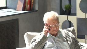 L'uomo anziano felice si siede in una sedia, leggendo il giornale e parla al telefono in un appartamento moderno video d archivio