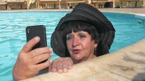 L'uomo anziano femminile senior caucasico in black hat sta parlando dalla video chiamata e sta nuotando in uno stagno di acqua bl video d archivio