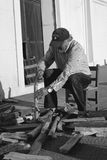 L'uomo anziano fende un certo legno Fotografie Stock Libere da Diritti