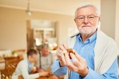 L'uomo anziano gioca con un puzzle di legno fotografie stock libere da diritti