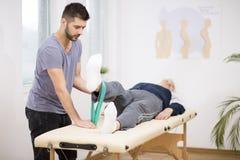 L'uomo anziano grigio si trova su una tavola e giovane medico lo aiuta durante gli esercizi immagini stock libere da diritti