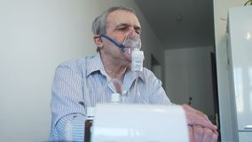 L'uomo anziano inala con la maschera di protezione del nebulizzatore archivi video