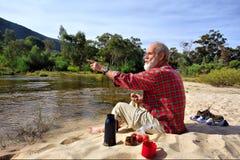 L'uomo anziano indica in qualche luogo mentre ha pranzo Fotografia Stock