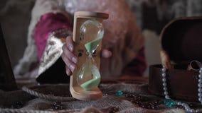 L'uomo anziano irriconoscibile con la barba lunga lancia gli orologi della sabbia stock footage