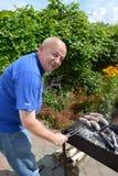 L'uomo anziano prepara le salsiccie una griglia su un addetto alla brasatura Fotografie Stock