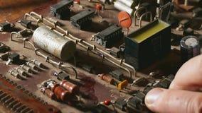 L'uomo anziano ripara il tecnico che della radio del chip il fumo è saldatoio venente della riparazione Riparazione del tecnico o video d archivio