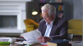 L'uomo anziano si preoccupa per le fatture considera sul calcolatore ed ottiene turbata stock footage