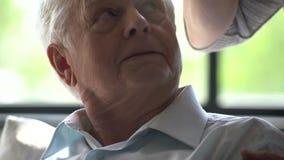L'uomo anziano si siede in sedia e parla al telefono in appartamento moderno poi passa il telefono alla sua moglie video d archivio