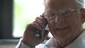 L'uomo anziano si siede in una sedia e parla al telefono in un appartamento moderno video d archivio