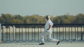 L'uomo anziano sportivo fa gli affondo vicino al fiume stock footage